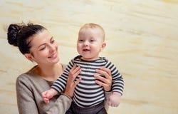 Junge Mutter, die ihr glückliches gesundes Baby hält Stockfoto