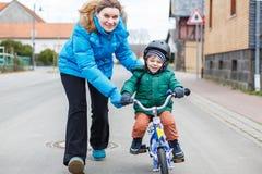 Junge Mutter, die ihr 2 Jahre alte beibringt, kleine Sohn, um ein Fahrrad zu reiten, Stockfotografie
