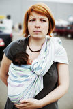 Junge Mutter, die ihr Kind in einem Riemen trägt stockbild