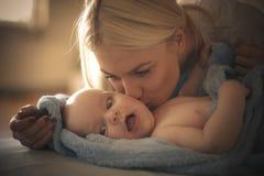 Junge Mutter, die ihr kleines Baby küsst stockfotografie