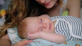 Junge Mutter, die ihr kleines schlafendes neugeborenes Baby küsst stock video footage