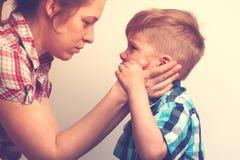 Junge Mutter, die ihr kleines schreiendes Kind tröstet Lizenzfreie Stockfotos