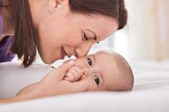 Junge Mutter, die ihr leichtes Baby streichelt Stockbild