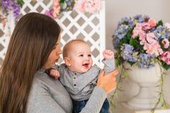 Junge Mutter, die ihr neugeborenes Kind hält Mutterkrankenpflegebaby Frau und neugeborener Junge im Raum Mutter, die mit spielt lizenzfreies stockbild