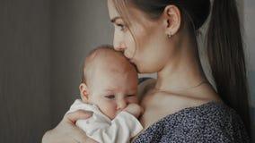 Junge Mutter, die ihr neugeborenes schlafendes Kind hält Familie zu Hause