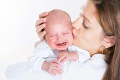 Junge Mutter, die ihr schreiendes neugeborenes Baby küsst Stockfotografie