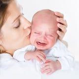 Junge Mutter, die ihr schreiendes neugeborenes Baby küsst Stockbild