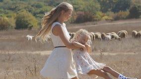 Junge Mutter, die ihre kleine Tochter nahe bei wirbelt stock footage