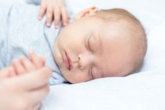 Junge Mutter, die ihre neugeborenes Kinderhand hält lizenzfreies stockfoto