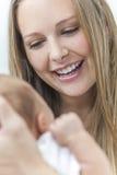 Junge Mutter, die an ihrem neuen Schätzchen lächelt Lizenzfreie Stockbilder