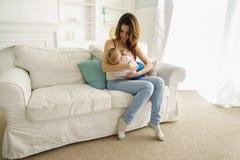 Junge Mutter, die ihren kleinen Sohn stillt lizenzfreie stockbilder