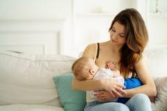 Junge Mutter, die ihren kleinen Sohn stillt lizenzfreies stockbild