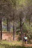 Junge Mutter, die ihren Sohn trägt und durch Holz geht Stockbilder
