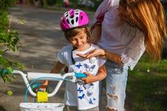 Junge Mutter, die ihrer Tochter beibringt, wie man Fahrrad im Park f?hrt lizenzfreies stockbild
