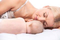 Junge Mutter, die im Bett mit Baby liegt Stockfotografie