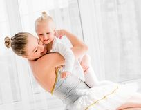 Junge Mutter, die kleine lächelnde Tochter im Ballettstudio umarmt lizenzfreie stockfotografie