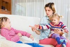 Junge Mutter, die kleine Tochter schilt Stockfotos