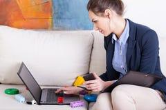 Junge Mutter, die Laptop verwendet, um zu Hause zu arbeiten Stockbilder