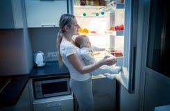 Junge Mutter, die Lebensmittel aus Kühlschrank heraus nachts nimmt, um etwas für ihr hungriges Baby zu kochen Lizenzfreies Stockbild
