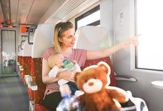 Junge Mutter, die mit Baby mit dem Zug reist lizenzfreie stockfotografie