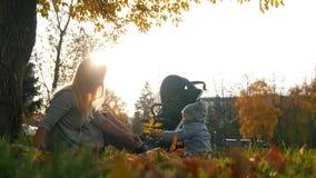Junge Mutter, die mit Blättern mit ihr lachendes kleines Baby im Herbstpark spielt lizenzfreies stockfoto