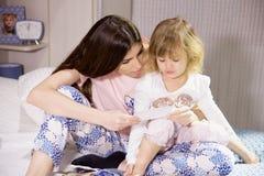 Junge Mutter, die mit blonder kleiner Tochter auf dem Bett zeigt Bild spielt Stockfotografie