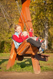 Junge Mutter, die mit dughter im Park schwingt Lizenzfreies Stockbild