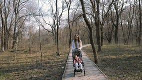 Junge Mutter, die mit einem Baby im Spaziergänger im Park geht stock video