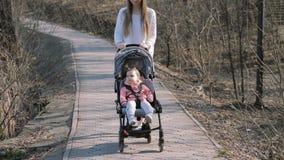 Junge Mutter, die mit einem Baby im Spaziergänger im Park geht stock video footage