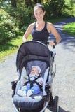 Junge Mutter, die mit einer Buggy rüttelt Lizenzfreies Stockfoto