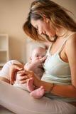 Junge Mutter, die mit ihrem Baby im Bett spielt Stockbilder