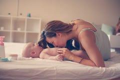 Junge Mutter, die mit ihrem Baby im Bett spielt Stockbild