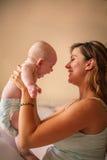 Junge Mutter, die mit ihrem Baby im Bett spielt Lizenzfreies Stockbild