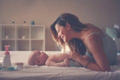 Junge Mutter, die mit ihrem Baby im Bett spielt Mutter, die i genießt Stockfotografie