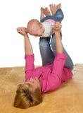 Junge Mutter, die mit ihrem Schätzchen spielt Stockbild