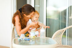 Junge Mutter, die Nebenschätzchen an der Terrasse speist Stockfotos