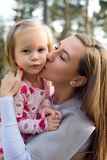 Junge Mutter, die nette Kleinkindmädchentochter in ihren Armen hält und ihr einen Kuss auf einer Backe gibt lizenzfreie stockbilder