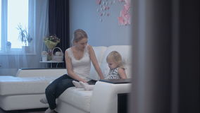 Junge Mutter, die nettes Kind lernt, wie man Tablette benutzt stock video footage
