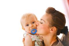 Junge Mutter, die Schätzchen mit soother küßt Stockfotos