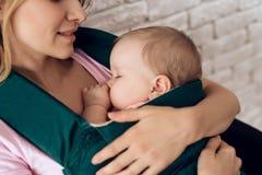 Junge Mutter, die schlafendes Baby im Babyriemen hält stockbilder