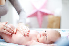 Junge Mutter, die Talkum an einem Schätzchen aufträgt Lizenzfreie Stockfotos