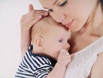 Junge Mutter, die um ihrem neugeborenen Baby sich kümmert Lizenzfreie Stockbilder