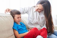 Junge Mutter, die versucht, ihr schreiendes Kind zu trösten und sich zu beruhigen stockfoto