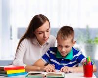 Junge Mutter, die zu Hause an einem Tisch hilft ihrem kleinen Sohn mit seiner Hausarbeit von der Schule sitzt, wie er Anmerkungen stockfoto