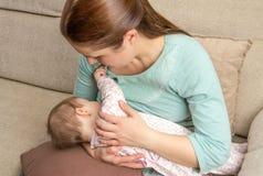 Junge Mutter, die zu Hause ihr Baby stillt Stockbild
