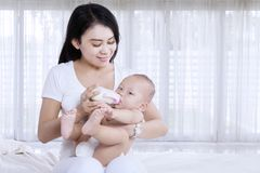 Junge Mutter, die zu Hause ihrem Baby Milch gibt Lizenzfreies Stockfoto