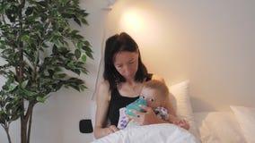 Junge Mutter, die zu Hause ihren Babysohn mit einer Flasche Milch einzieht stock video