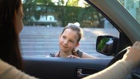 Junge Mutter in einem Auto ihre Tochter zur Schule weg sehend stock footage