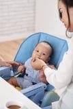 Junge Mutter-Fütterungsbaby stockbild