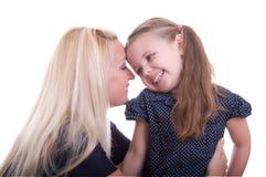 Junge Mutter flüstert ein Geheimnis Stockfoto